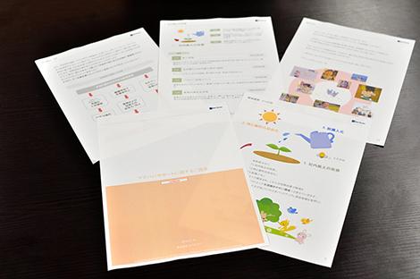 ママパパサポートプロジェクト提言書 子どもたちの写真やかわいいイラストでも訴求! プロジェクトメンバー(一部)、前列中央が小澤さん